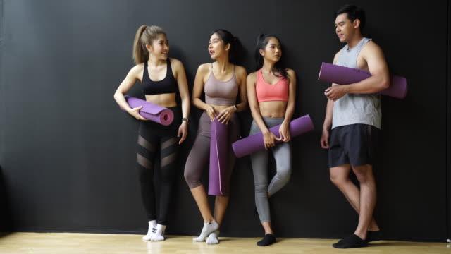 glad leende man och kvinnor ha kul att prata i gymmet. grupp av ungdomar koppla av i gymmet efter träningen. - gym skratt bildbanksvideor och videomaterial från bakom kulisserna