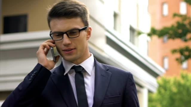 glücklich lächelnden mann in anzug spricht smartphone auf straße, profitable-city-vertrag - billionär stock-videos und b-roll-filmmaterial