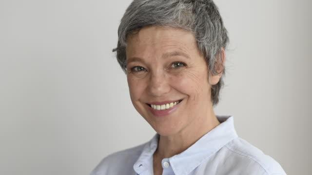 mutlu gülümseyen olgun kadın - doğal koşul stok videoları ve detay görüntü çekimi