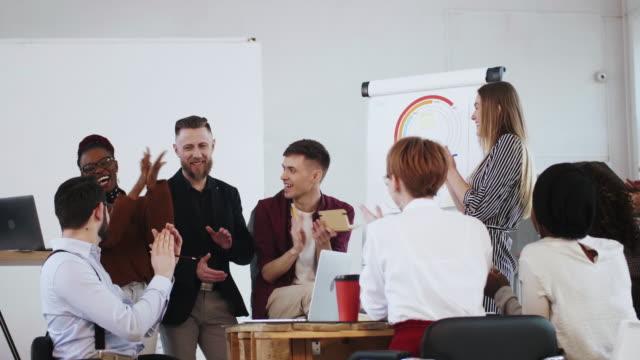 glücklich lächelnde multiethnische gruppe von geschäftsleuten, die bei einem seminartreffen am bürotisch zu einer jungen rednerin klatschen. - dankbarkeit stock-videos und b-roll-filmmaterial