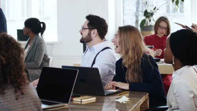 Happy smiling multiethnic office managers sit at table, laugh at corporate training seminar at modern healthy workplace. video