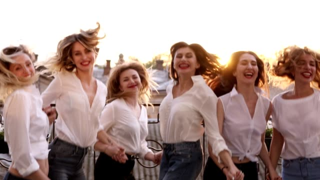 happy smiling outside on a balcony terrace. building, city landscape background jumping together in slow motion. having fun together, fashionable female in same clothes laughing. enjoyment life - bachelorette party stock videos and b-roll footage