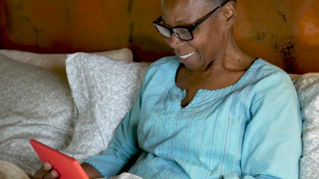 glad leende äldre svart kvinna som använder sin digitala tablett för en videochatt - blåsa en kyss bildbanksvideor och videomaterial från bakom kulisserna