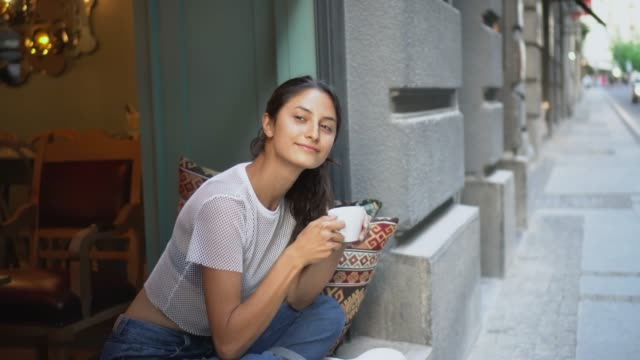 Happy smiling woman drinking coffee and waving to a friend