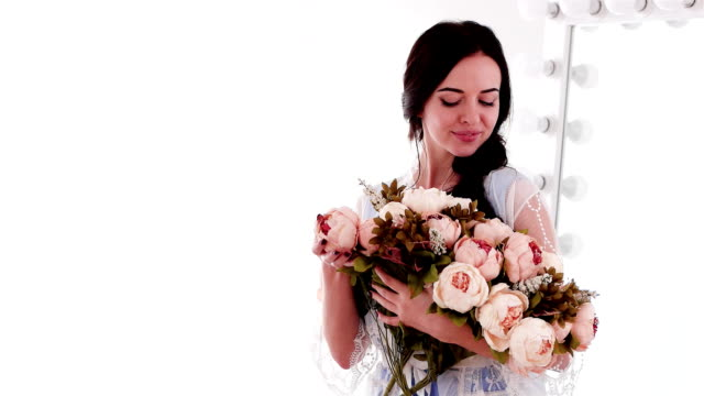 happy smiling woman holding huge pink and beige bouquet of peonies, long-haired girl video