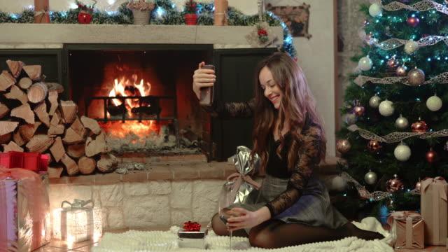 glad leende kvinna i eleganta kläder sitter bredvid den brinnande spisen och glödande gran och med videosamtal med familjemedlemmar eller vänner. ganska kvinnlig prata med människor, visar - wine box bildbanksvideor och videomaterial från bakom kulisserna