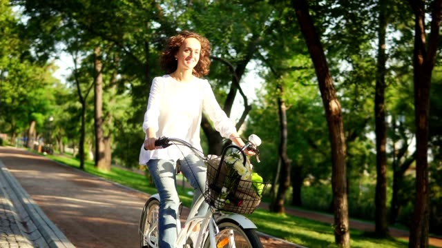 happy smiling woman is enjoying her time riding a city bicycle with a basket and flowers inside during the dawn. steadicam shot. slowmotion - cestino della bicicletta video stock e b–roll