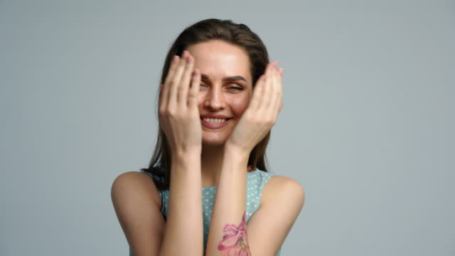 Happy smiling woman playing hide and seek and covering her face with palms