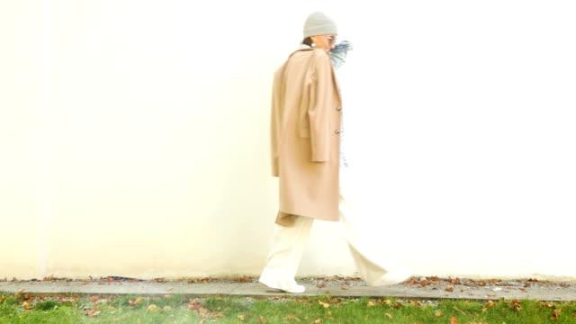 vídeos y material grabado en eventos de stock de feliz mujer sonriente camina en la calle, se detiene y posa para la cámara de estilo de varias capas traje de moda - moda de otoño