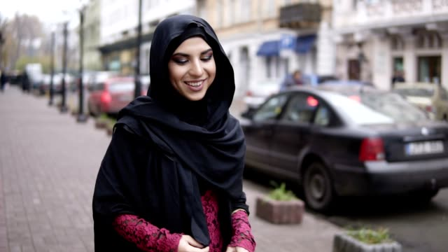 happy smiling young attractive woman in black hijab walking in the street in city. slowmotion shot - arab filmów i materiałów b-roll