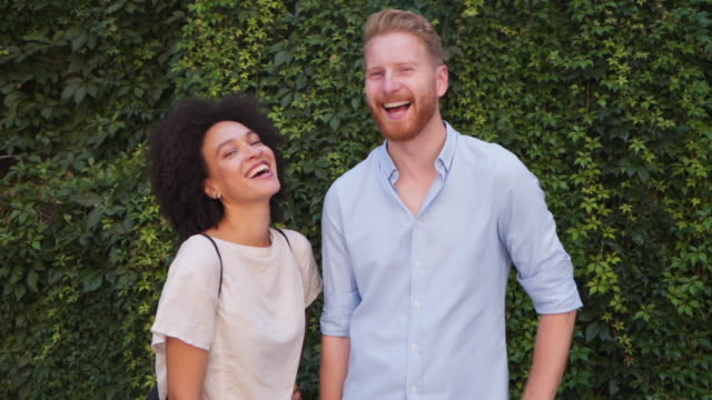 Happy smiling young couple Two people, mixed race woman, and readhead man, smiling at camera charming stock videos & royalty-free footage