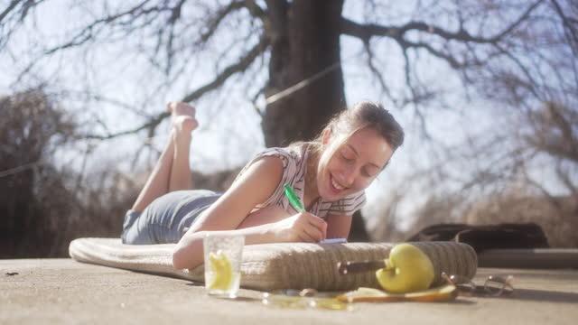 felice sorridente giovane hipster donna, scrive il suo diario, mentre lei è in condizioni spirituali dopo aver prende alcuni funghi commestibili - china drug video stock e b–roll