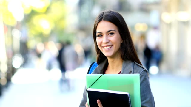 Happy student posing in the street Portrait of a happy student posing holding folders and looking at camera in the street university student stock videos & royalty-free footage