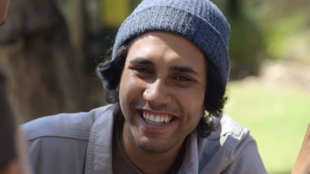 Happy Student Close-up of a happy young aboriginal male student talking with his peers outdoors. minority groups stock videos & royalty-free footage