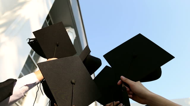 happy students in gowns throwing mortarboards in the air.education, graduation and people concept - - tocco accademico video stock e b–roll