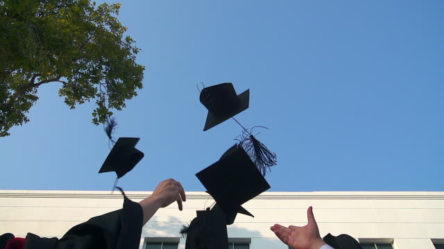 Happy students in gowns throwing mortarboards in the air.Education, graduation and people concept - video