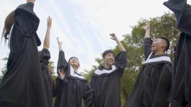 happy  students in graduation gowns holding diplomas on university campus - tocco accademico video stock e b–roll