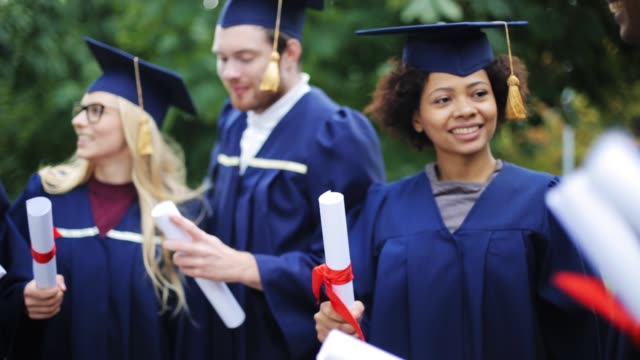 happy students in mortar boards with diplomas education, graduation and people concept - group of happy international students in mortar boards and bachelor gowns with diplomas diploma stock videos & royalty-free footage