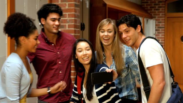 Happy students taking selfie in locker room video