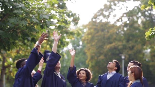 happy students throwing mortar boards up - graduation cap stock videos & royalty-free footage