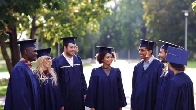 happy students throwing mortar boards up - tocco accademico video stock e b–roll