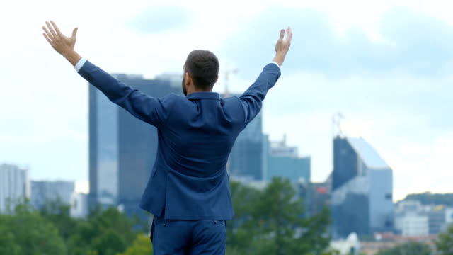 Happy Successful Business Man Raises His Hands, He Has His Business Victory. In The Background Big City with Skyscrapers. video