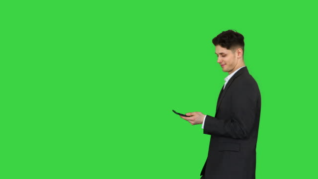 vídeos de stock e filmes b-roll de happy successful businessman dancing listening music from the phone and walking on a green screen, chroma key - ignorância