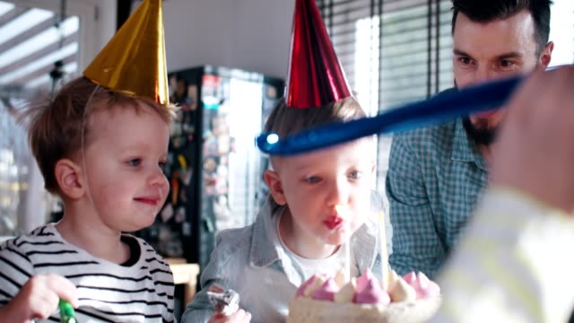 Happy sweet little Caucasian boy child struggles blowing on birthday cake, celebrating fun party at home slow motion.