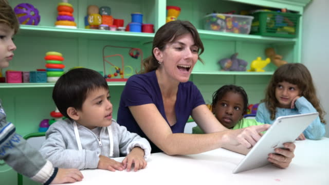 Happy teacher narrating story with digital tablet video