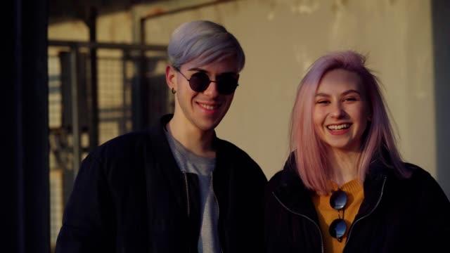 stockvideo's en b-roll-footage met gelukkig tiener paar glimlachend - roze haar