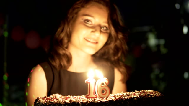 Happy teen girl at 16 birthday party holding cake and burning candles smiling and having fun, handheld shot