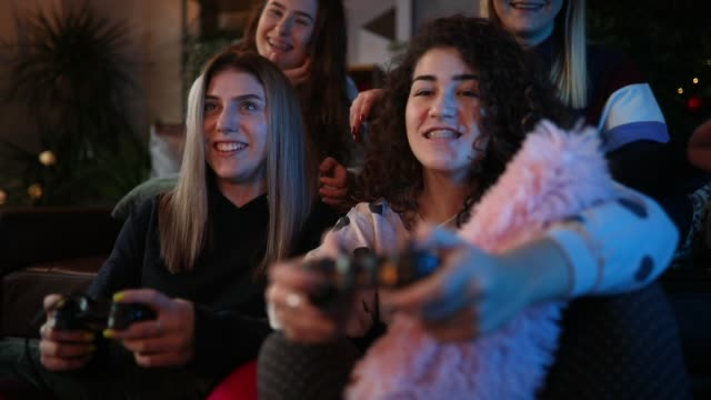Happy teen girls playing video games