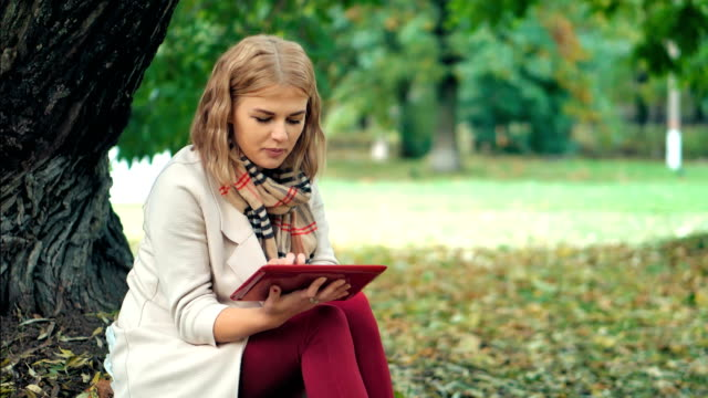 Happy teen woman relax in autumn park. Yellow trees, beautiful fall time video