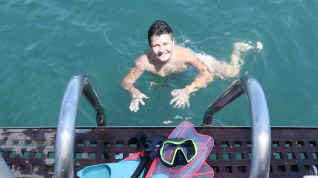 Happy teenage boy in sea at summer vacation