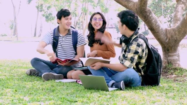vidéos et rushes de heureux chez les adolescents garçons et fille lisant un livre à l'extérieur. teenage copines s'amuser et rire. - pots de bureau