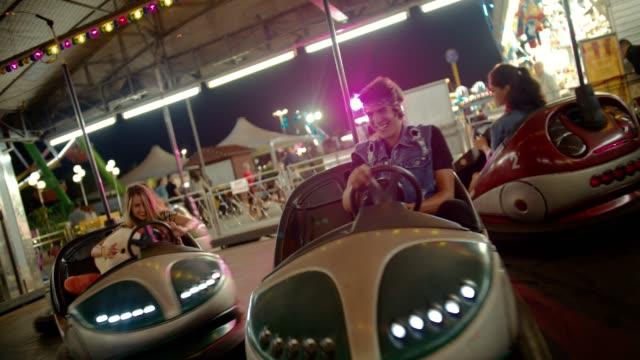 Happy teenage friends driving bumper cars at funfair at night