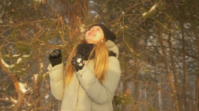 Happy teenager girl enjoy snowfall in winter pine tree forest sunny day and cover with hood