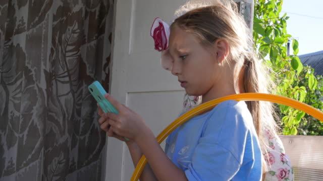 vídeos de stock, filmes e b-roll de menina adolescente feliz usando o telefone celular para comunicação engraçada com demônios - primeira comunhão