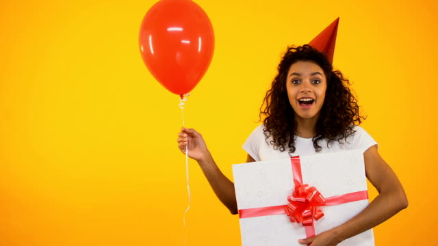 Happy teenager holding balloon and huge giftbox, celebrating birthday, greetings Happy teenager holding balloon and huge giftbox, celebrating birthday, greetings birthday background stock videos & royalty-free footage
