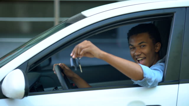 Happy teenager showing car key to window sitting on driver seat of new vehicle