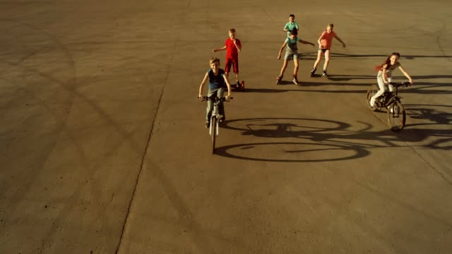 Happy teenagers are riding on bikes, roller skates and scooters. Bird's eyes view video