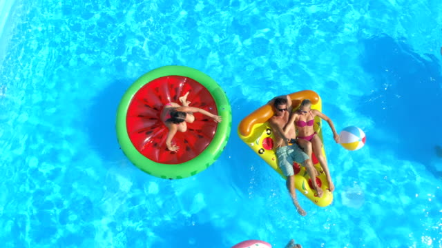 vídeos de stock e filmes b-roll de aerial: happy teenagers having fun on inflatable colorful floats in pool water - brinquedos na piscina
