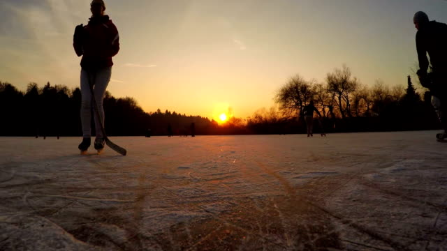 FPV LOW ANGLE: Happy teenagers iceskating and playing hockey at magical sunset video