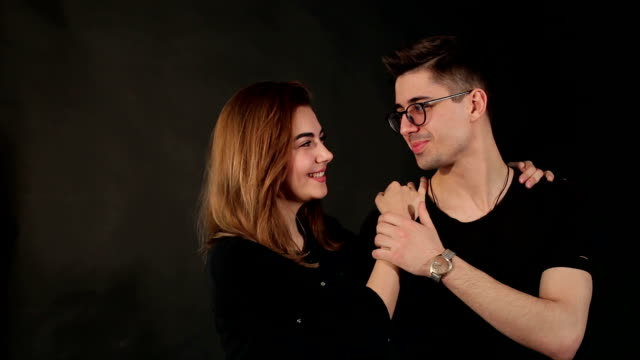 happy teens hugging on black background, portrait. - brunette woman eyeglasses kiss man video stock e b–roll