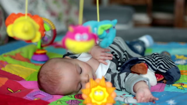 Happy three months old baby boy, playing at home on a colorful activity blanket, toys and different activity around him video