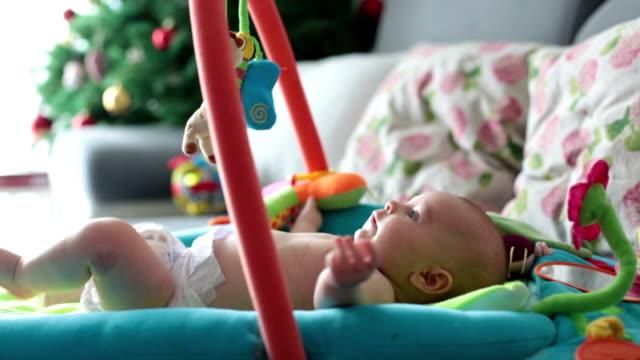 vídeos de stock, filmes e b-roll de menino feliz três meses de idade, jogando em casa em um cobertor de atividade coloridos, brinquedos e diferentes atividades em torno dele - mobile