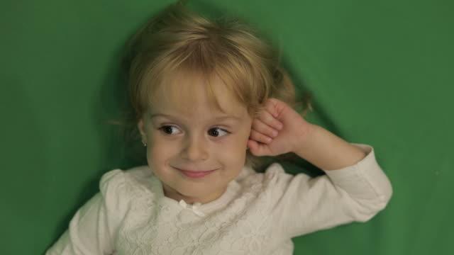 lyckliga tre år gammal flicka. söt blond barn. bruna ögon. grön skärm - människohuvud bildbanksvideor och videomaterial från bakom kulisserna