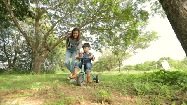 Happy time, Mother helping little boy ride tricycle in the park, slow motion