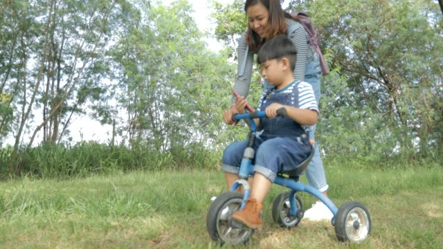 Happy time, Mother helping little boy ride tricycle in the park