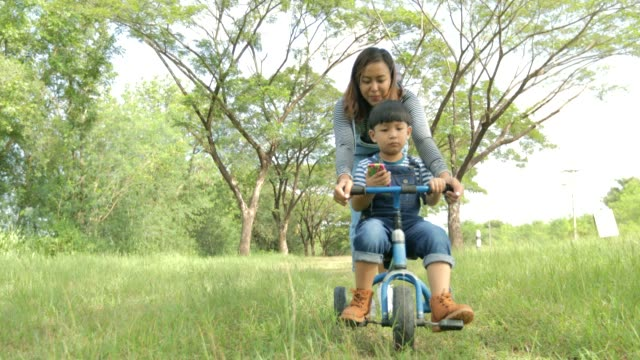 Happy time, Mother helping little boy ride tricycle in the park, Thailand